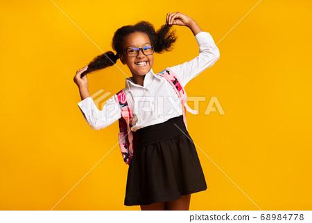 Joyful Black Schoolgirl Playing With Ponytails Posing On Yellow Background 68984778