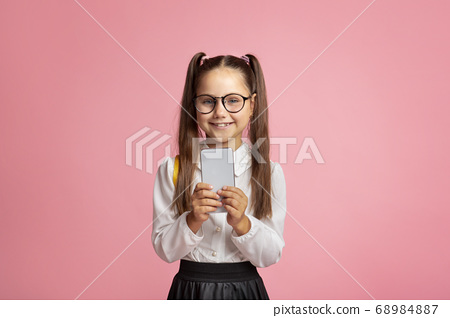 Modern technology and school. Smiling little girl with glasses holding smartphone 68984887