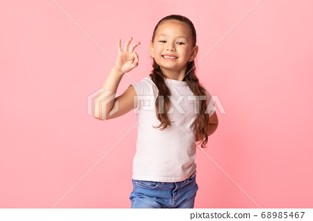 Asian girl showing ok gesture and smiling 68985467