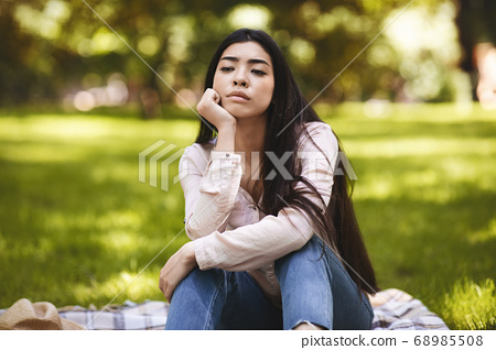 Summertime Sadness. Portrait Of Thoughtful Asian Woman Sitting On Plaid In Park 68985508