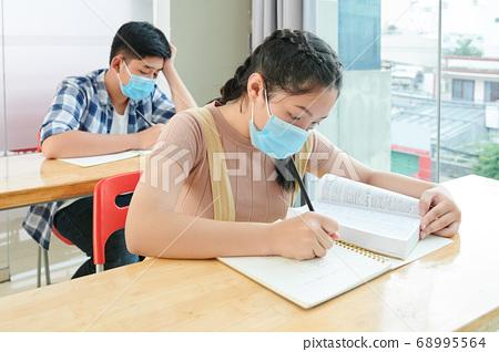 School children writing in copybooks 68995564