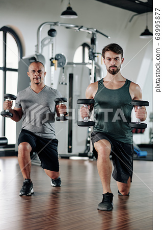 Men doing lunges with weights 68995877