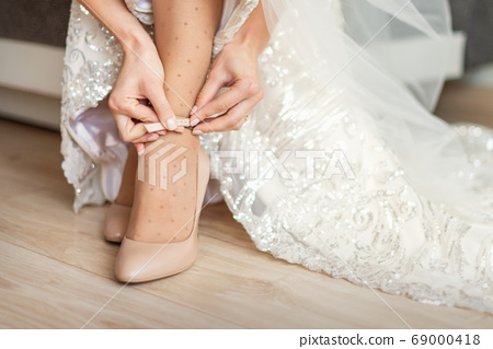 Bride puts on wedding shoes 69000418