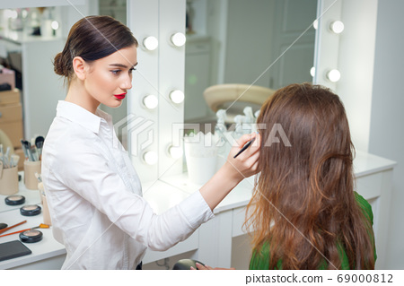 Makeup artist working with client. 69000812