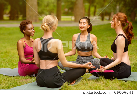 Outdoor yoga. Multinational women sitting in circle and meditating at park 69006041