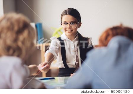 Dark-haired girl explaining lesson to her classmates 69006480