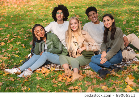 Young carefree friends sitting on the ground at public park 69006513