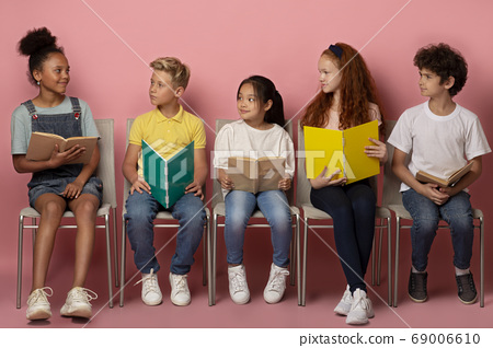Industrious multinational schoolchildren with study materials sitting on chairs on pink background 69006610