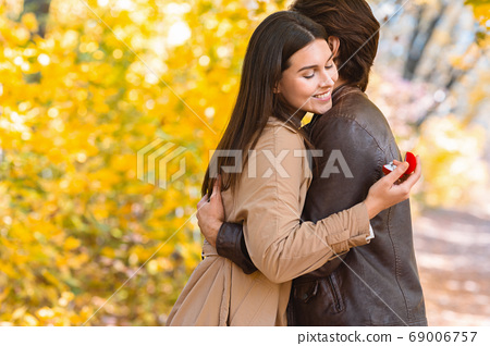 Woman looking at proposal ring while hugging her boyfriend 69006757