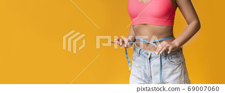 Slim Unrecognizable Woman Measures Her Waist With Measuring Tape, Yellow Background 69007060