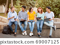 Multicultural Students Learning Together Working On Group Project Sitting Outside 69007125