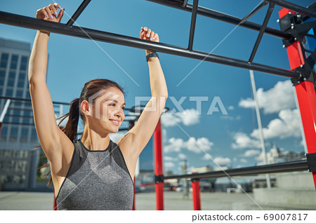 Positive delighted woman pulling up on the bar 69007817