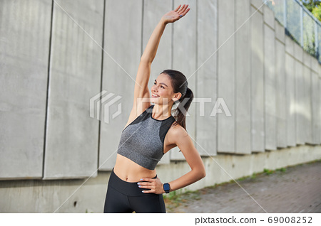 Positive delighted young sportswoman raising her arm 69008252
