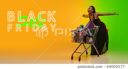 Portrait of young woman in neon light on gradient backgound. The human emotions, black friday, cyber monday, purchases, sales, finance concept. Neoned lettering. 69008577