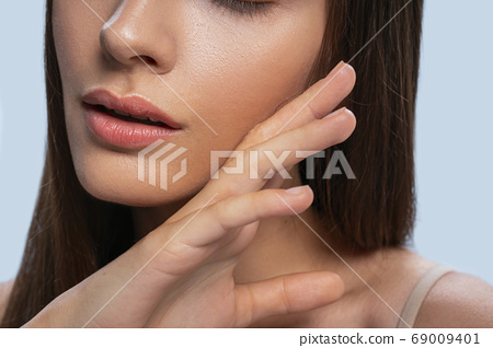 Placid lady touching her face with the right hand 69009401
