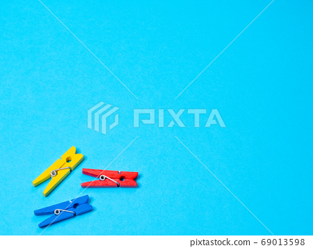 Red, blue and red wood clothespins pegs on blue background 69013598