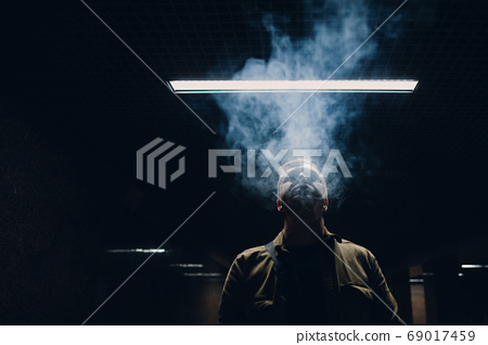 Portrait of young caucasian man smoking e-cigarette in dark with line light 69017459
