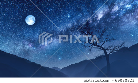 Night sky with moon and milky way over mountains 69020823