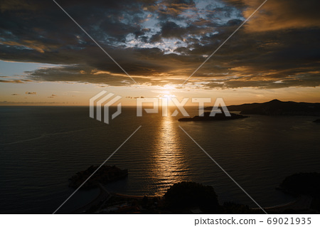 Sunny path on the water, from sunset in the blue sky among clouds and clouds, in Montenegro, near the island of Sveti Stefan. 69021935