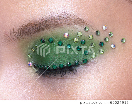 Closed eye with green crystals and green eyeshadow 69024912