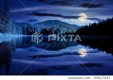 mountain lake among the forest at night. trees in colorful folia 69027843