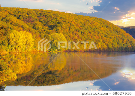 mountain lake among the forest at sunset. trees in colorful foli 69027916