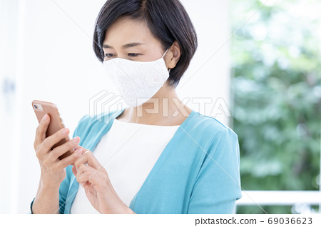 Middle woman: A woman wearing a fashionable mask and calling 69036623