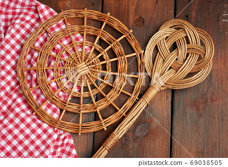 spoon and round wicker stand for pots on a brown wooden table 69038505