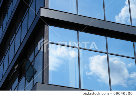 facade of a modern building on a bright Sunny day, blue sky and clouds reflecting in a glass, beautiful exterior of the new building 69040300