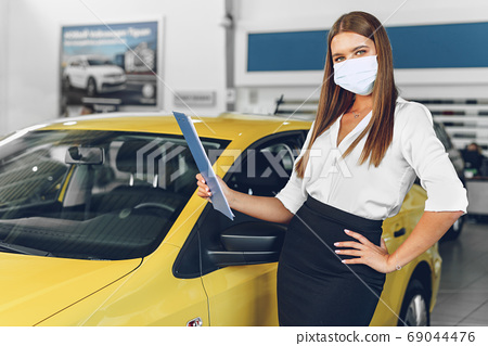 Woman car seller standing near new car wearing protective face mask 69044476