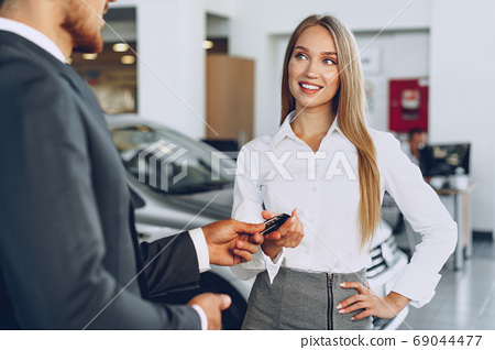 Young attractive woman buying a new car in car salon 69044477