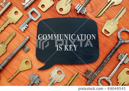 Communication is key quote. Black nameplate on a wooden background. 69049545