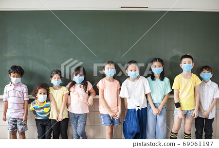Group of diverse young students wear mask and standing together in classroom 69061197