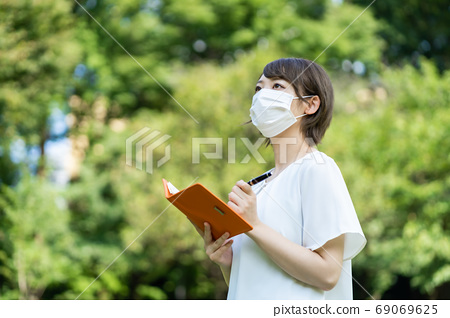 一個年輕的女人,走路與新的電暈肺炎手冊 69069625