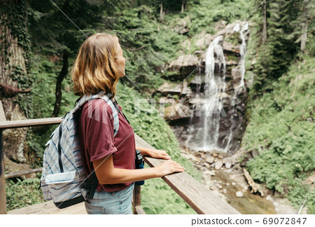 woman with backpack by the waterfall 69072847