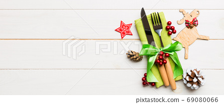 New year set of Banner fork and knife on napkin. Top view of christmas decorations and reindeer on wooden background. Holiday family dinner concept with empty space for your design 69080066