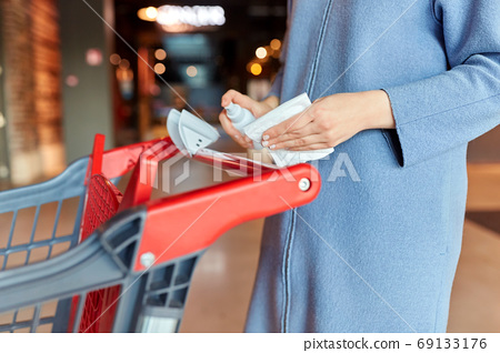 woman cleaning shopping cart handle with sanitizer 69133176