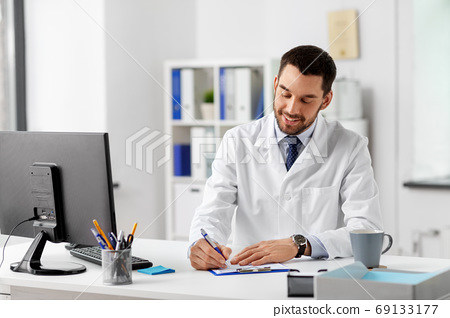 smiling male doctor with clipboard at hospital 69133177