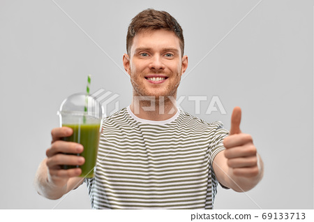 happy man with green smoothie showing thumbs up 69133713