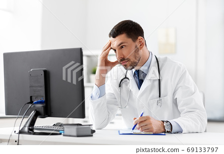 doctor with clipboard and computer at hospital 69133797
