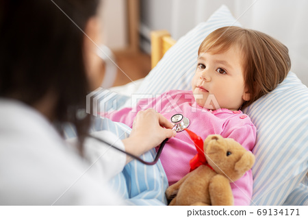 doctor with stethoscope and sick girl in bed 69134171