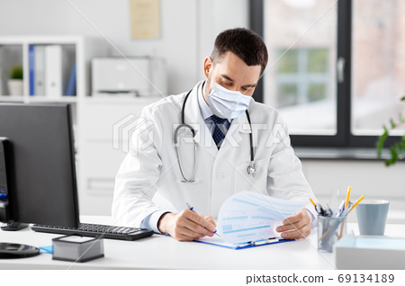 smiling male doctor with clipboard at hospital 69134189