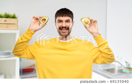 happy young man in yellow sweatshirt with avocado 69135040