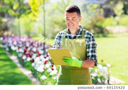 happy man with clipboard at summer garden 69135420
