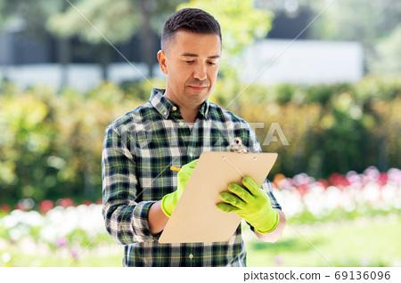 man with clipboard at summer garden 69136096