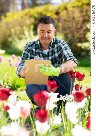 man with clipboard and flowers at summer garden 69136470
