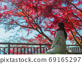 Rear view of woman admiring the beautiful autumn scenery 69165297