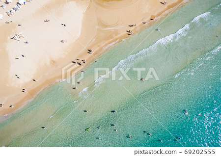 Aerial view of a shallow sandy beach and sunshade.Tourism and holiday concept. 69202555