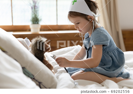 Nurse kid use stethoscope listen heartbeat of soft hedgehog toy 69202556