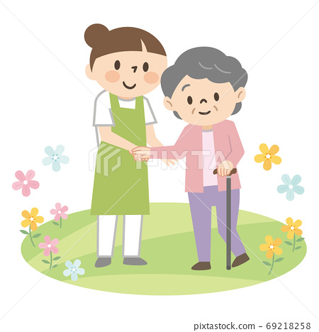 Young female caregiver assisting an elderly woman with a cane 69218258
